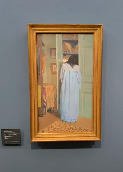 Intérieur, femme en bleu fouillant dans une armoire